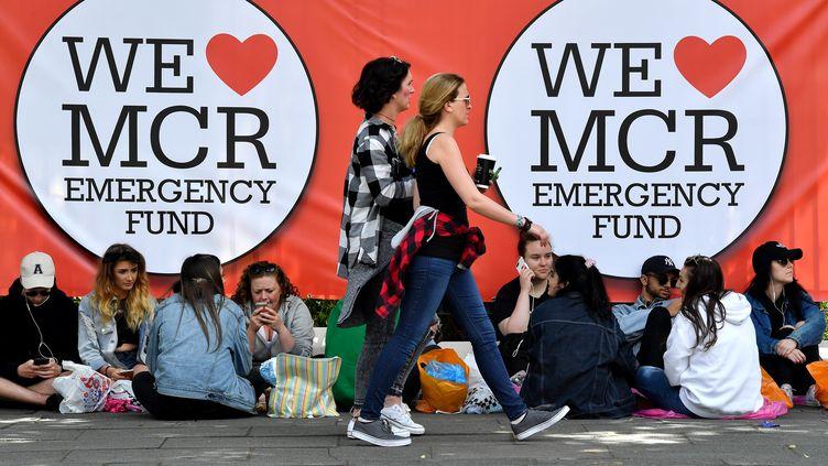 """Des personnes attendent, le 4 juin 2017, pour assister au concert """"One Love Manchester"""", en hommage aux victimes de l'attentat qui a eu lieu le 22 mai dans la ville britannique. (ANTHONY DEVLIN / AFP)"""