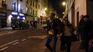 Les gens fuient un rassemblement au restaurant Le Carillon, l'un des sites des attentats, après un mouvement de foule, le 15 novembre 2015 à Paris. (DOMINIQUE FAGET / AFP)