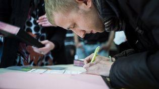 Un jeune homme signe un contrat d'avenir, le 17 mai 2013 à Beauvais (Oise). (FRED DUFOUR / AFP)