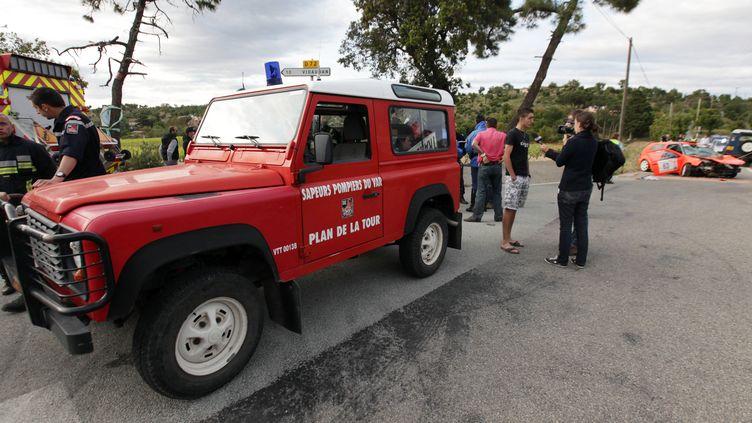 Pompiers et gendarmes s'affairent autour de la voiture de rallye accidentée dont la sortie de route a fait deux morts à Plan-de-la-Tour (Var), le 19 mai 2012. (JEAN-CHRISTOPHE MAGNENET / AFP)