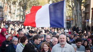 Le drapeau français brandi par des personnes rassemblées en hommage aux victimes des attentats du 13 novembre le 22 novembre 2015 à Toulouse (Haute-Garonne). (CITIZENSIDE / PABLO TUPIN / AFP)