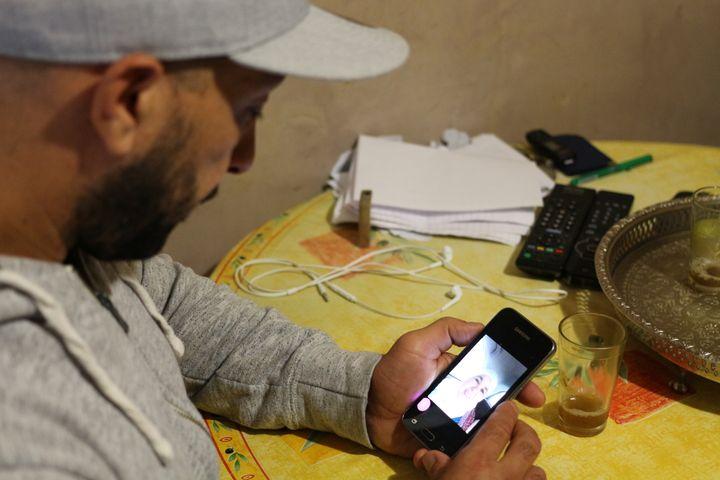 Ali Charrihi regardant une photo de sa mère, Fatima, sur son téléphone portable, le 13 octobre 2016 à Nice (Alpes-Maritimes). (BENOIT ZAGDOUN / FRANCEINFO)