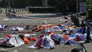 Des policiers anti-émeute turcs bloquent l'accès au site de l'attentat où les corps des victimes sont recouverts de banderoles et de drapeaux, le 10 octobre 2015 à Ankara (Turquie). (ADEM ALTAN / AFP)