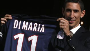 Le joueur de football argentin Angel Di Maria montre son nouveau maillot du Paris Saint Germain lors d'une conférence de presse le 6 août 2015 à Paris. (CHRISTIAN HARTMANN / REUTERS )
