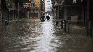 Des secouristes progressent dans les rues inondées de Macao, en Chine, le 16 septembre 2018. (ISAAC LAWRENCE / AFP)