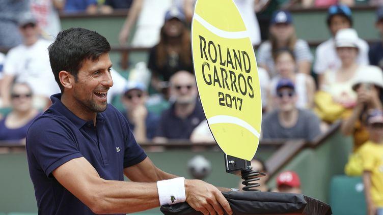 Novak Djokovic fait le pitre sur le court, en attendant le début du tournoi. (FRANCOIS-XAVIER MARIT / AFP)