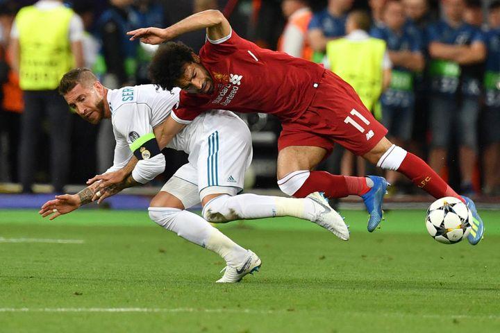 L'attaquant égyptien de Liverpool Mohamed Salah tombe avec le défenseur espagnol du Real Madrid Sergio Ramos lors de la finale de l'UEFA Champions League entre Liverpool et le Real Madrid au stade olympique de Kiev, en Ukraine, le 26 mai 2018. (GENYA SAVILOV / AFP)