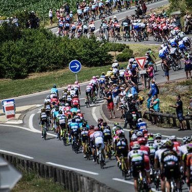 Les coureurs du Tour de France franchissent un rond-point, lors d'une étape en Vendée, entre Mouilleron-Saint-Germain et La Roche-sur-Yon, le 8 juillet 2018. (JEFF PACHOUD / AFP)