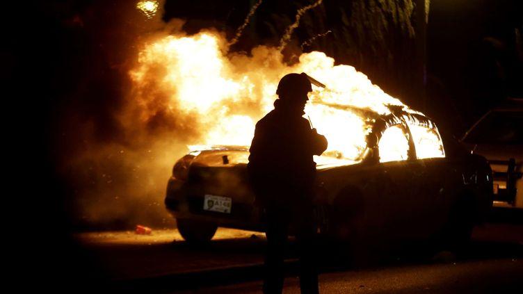 Un pompier contemple une voiture de police incendiée par des manifestants, lundi 24 novembre, à Ferguson (Missouri, Etats-Unis). (CHARLIE RIEDEL / AP / SIPA)