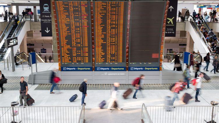 Des passagers passent devant un panneau d'affichage des vols à l'aéroportParis-Charles-de-Gaulle, le 24 septembre 2014. (MAXPPP)