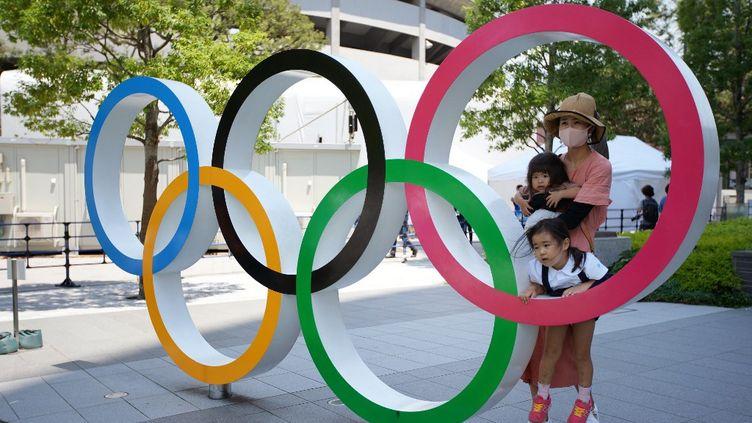 Des Japonais posent derrière l'emblème des JOà côté du stadeolympiqueà Tokyo, le 20 juillet 2021. (NAOKI MAEDA / YOMIURI / AFP)