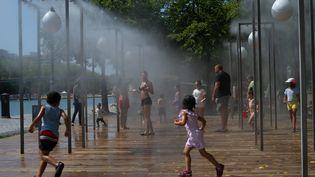Enfants et adultes cherchent à se rafraîchir à Paris, le 9 août 2020. (PATRICIA MORIBE / HANS LUCAS / AFP)