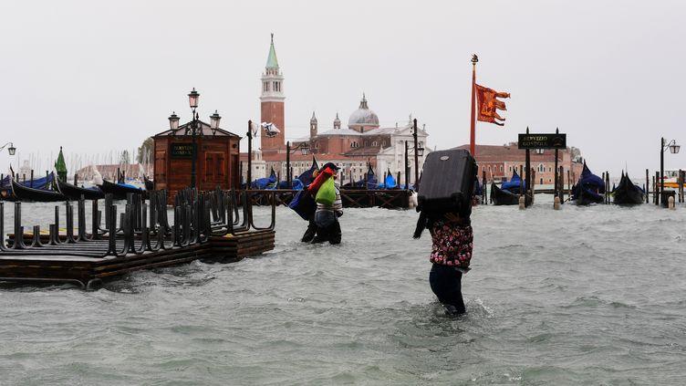 Une femme porte une valise à Venise, sous les eaux, le 29 octobre 2018. (MIGUEL MEDINA / AFP)