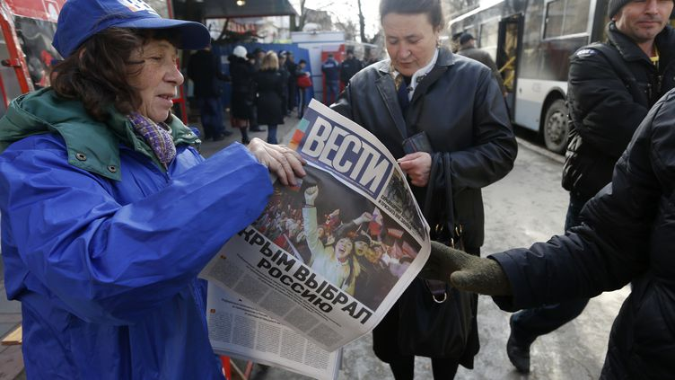 Des habitants de Simferopol, en Crimée, découvrent la une des journaux au lendemain du référendum en faveur au rattachement à la Russie, lundi 17 mars 2014. (VASILY FEDOSENKO / REUTERS )