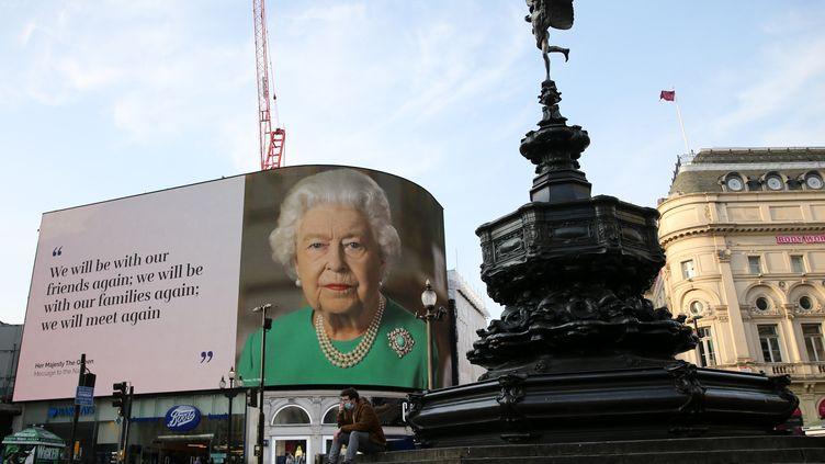 Un message de la reine Elizabeth II à propos de l'épidémie de coronavirus est affiché à Picadilly Circus, à Londres, le 9 avril 2020. (ISABEL INFANTES / AFP)