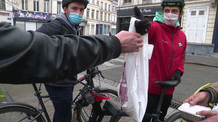 Tanguy et Thibaud, bénévoles du mouvement #PourEux, livrent des repas aux sans-abris à Lille. (J. Vasco / France 3)