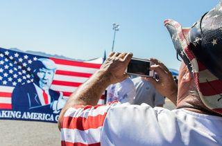 Randal Thom, éleveur du Minnesota, prend des photos lors d'un meeting de Donald Trump, le 19 octobre 2018. (VALENTINE PASQUESOONE / FRANCEINFO)