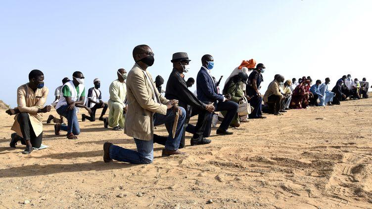 Des manifestants, genou à terre à Dakar (Sénégal), rassemblés pour soutenir le mouvement Black Lives Matter après la mort de George Floyd aux Etats-Unis, tué lors de son interpellation par des officiers de la police de Minneapolis. (SEYLLOU / AFP)