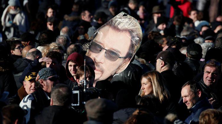 Des fans du chanteur brandissent un portrait de Johnny Hallyday sur les Champs-Elysées. (BENOIT TESSIER / REUTERS)