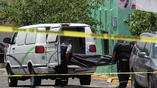 Du personnel médico-légal charge le corps d'une personne tuée lors d'une opération de police qui a fait trois morts àGuadalajara, au Mexique, le 10 juin 2018. (ULISES RUIZ / AFP)