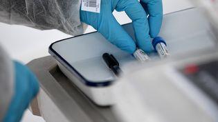 Un biologiste travaille sur un prélèvement de malade du Covid-19. (FRANCK FIFE / AFP)