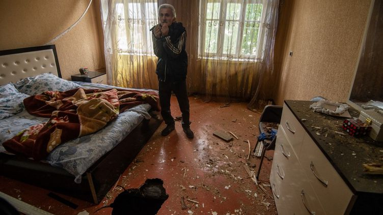 Un résident local montre un trou dans le sol endommagé par les récents bombardements dans sa maison, dans la ville d'Ivanyan, à l'extérieur de Stepanakert, la République autoproclamée du Haut-Karabakh, le 1er octobre 2020. (ASATUR YESAYANTS / SPUTNIK / AFP)