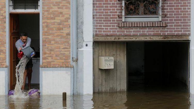Un homme déverse de l'eau de sa maison inondée à Villeneuve-Saint-Georges (Val-de-Marne), le 3 juin 2016. (CHRISTIAN HARTMANN / REUTERS)