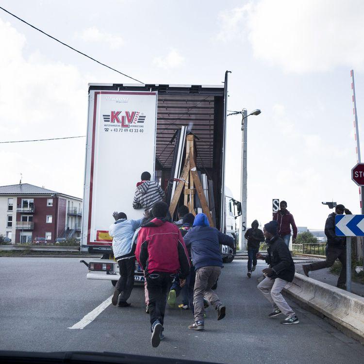Des migrants profitent du fait qu'un camion à destination de l'Angleterre s'arrête à un stop pour tenter de s'introduire à l'intérieur, le 9 octobre 2014, à Calais. (MAXPPP)