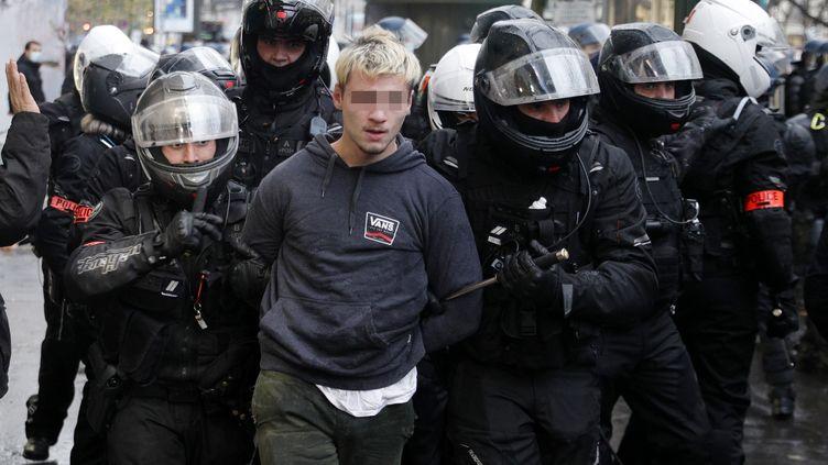 """Des policiers arrêtent un jeune homme le 12 décembre 2020 à Paris durant la manifestation contre la proposition de loi sur la """"sécurité globale"""". (GEOFFROY VAN DER HASSELT / AFP)"""