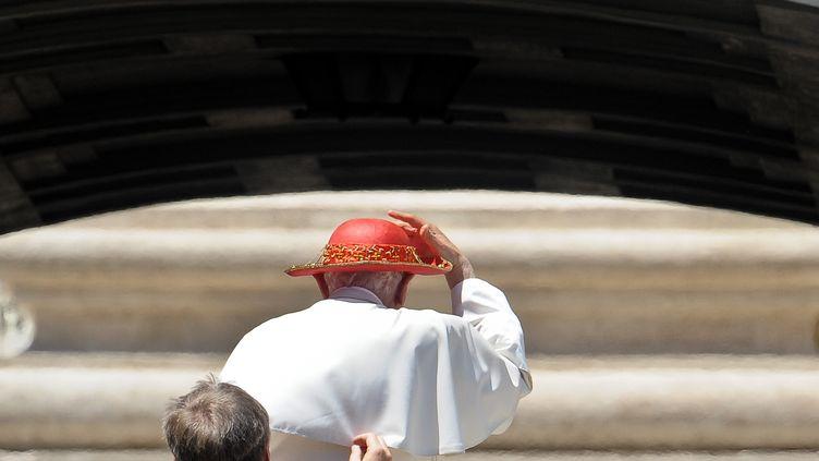 Benoît XVI réajuste son chapeau sur la place Saint-Pierre de Rome, le 15 juin 2011 (ANDREAS SOLARO / AFP)