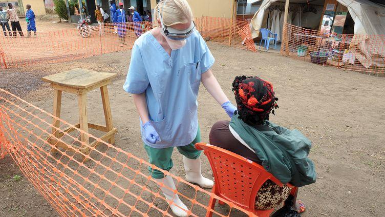 """Une infirmière de l'ONG """"Médecins sans frontières"""" examine une patiente dans un centre pour les victimes du virus Ebola à Guekedou (Guinée), le 1er avril 2014. (SEYLLOU / AFP)"""