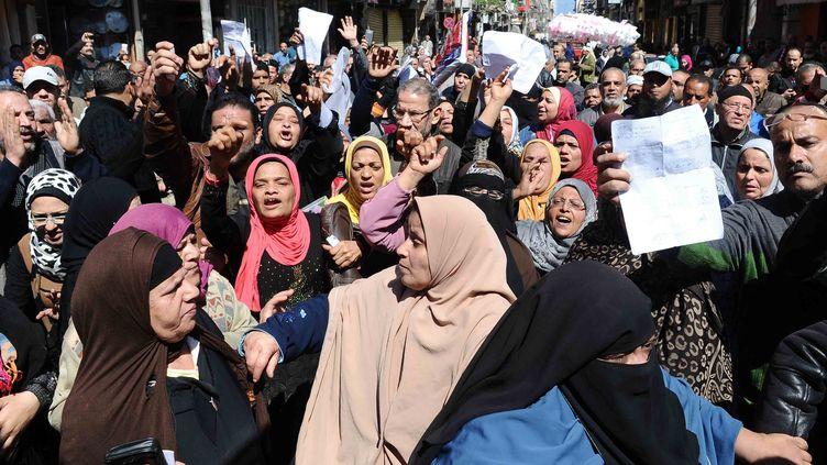 Des dizaines d'Egyptiens ont manifesté le 7 mars 2017 devant un bureau du gouvernement dans le centre-ville d'Alexandrie contre la décision du ministère de l'Approvisionnement de limiter la distribution de pain subventionné aux détenteurs d'un nouveau système de cartes numériques. (STR / AFP)