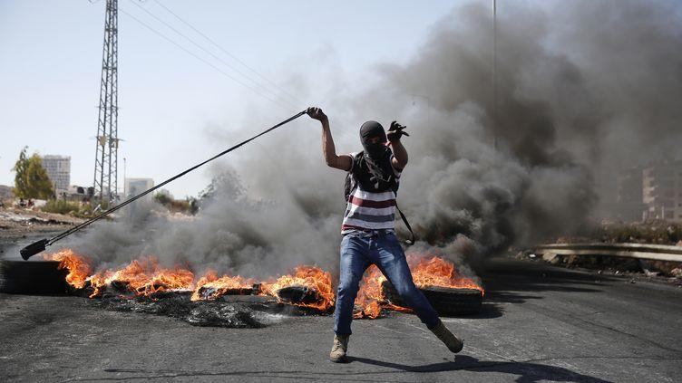 Un Palestinien affronte à coup de jets de pierre des soldats israéliens le 11 octobre 2015 près deRamallah en Cisjordanie. (ABBAS MOMANI / AFP)