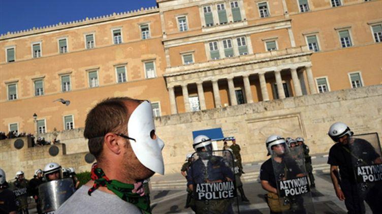 Un manifestant masqué près d'un cordon policier devant le Parlement grec à Athènes (AFP - DIMITAR DILKOFF)