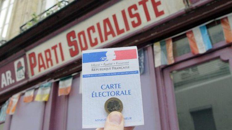 Un sympathisant présente sa carte électorale ainsi qu'une pièce d'un euro devant une permanence du Parti socialiste à Paris en janvier 2011 (JACQUES DEMARTHON / AFP)