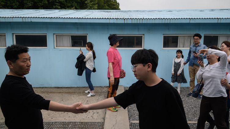 Des visiteurs pennent la pose sur la réplique de ligne de démarcation de Panmunjom, le 5 mai 2018. (ED JONES / AFP)