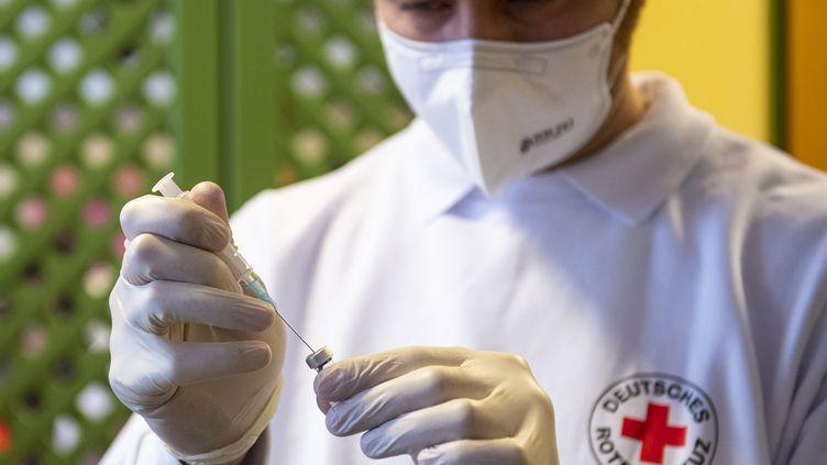 Un médecin de la Croix Rouge allemande prépare une dose de vaccin contre le Covid-19, le 27 décembre 2020, à Zolling. (LENNART PREISS / AFP)