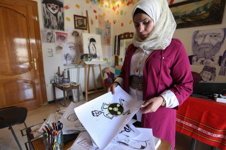"""L'artiste syrienne Amani al-Ali, dans son atelier d'Idleb.""""Ce que j'entends le plus, c'est que je suis une femme et que je ne devrais pas dessiner de telles choses"""", confie-t-elle. (OMAR HAJ KADOUR / AFP)"""