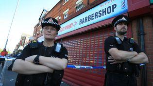 Des policiers devant un barbier, perquisitionné dans le cadre de l'enquête sur l'attentat de la Manchester Arena, le 26 mai 2017, dans le quartier de Moss Side à Manchester. (LINDSEY PARNABY / AFP)