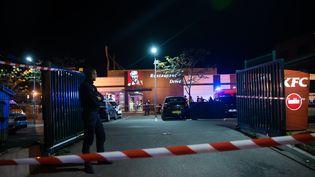 Des policiers enquêtent sur le parking d'un fast-food où deux hommes ont été trouvés morts par balle, à Marseille (Bouches-du-Rhône), le 21 octobre 2016. (BERTRAND LANGLOIS / AFP)