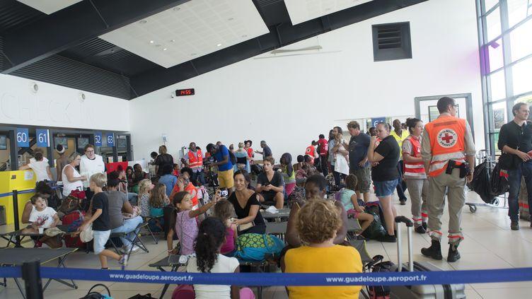 Des familles évacuées de Saint-Martin attendent à l'aéroport de Pointe-à-Pitre, en Guadeloupe, le 9 septembre 2017. (HELENE VALENZUELA / AFP)