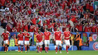 (La vague rouge des supporters gallois devant l'équipe qualifiée pour les 8e de finale © MaxPPP)