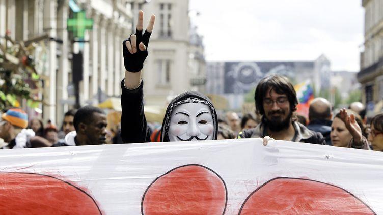 """Un """"Indigné"""" portant le masque de Guy Fawkes manifeste à la veille du premier tour de la présidentielle, à Paris, le 21 avril 2012. (KENZO TRIBOUILLARD / AFP)"""