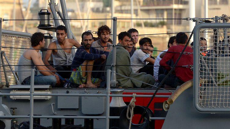 Des migrants arrivent dans le port de La Valette (Malte) après avoir été secourus en mer, le 12 octobre 2013. (MATTHEW MIRABELLI / AFP)
