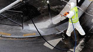 Un employé municipal désinfecte la rue, le 14 avril 2020 à Cannes (Alpes-Maritimes). (EMMANUEL FRADIN / HANS LUCAS / AFP)
