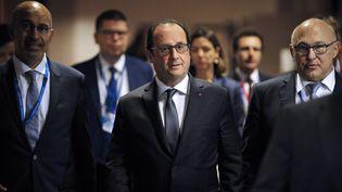 François Hollande, encadré par Harlem Désir, secrétaire d'Etat aux Affaires européennes, et Michel Sapin, ministre des Finances, le 13 juillet 2015 à Bruxelles (Belgique). (JEAN-CHRISTOPHE VERHAEGEN / AFP)