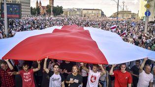 Sous un drapeau blanc et rouge qui est le signe de ralliement des opposants, une manifestation géante conteste la réélection d'Alexandre Loukachenko à la tête de la Biélorussie, le 16 août 2020 à Minsk. (SERGEI GAPON / AFP)