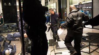 Des policiers sécurisent un magasin des Champs-Élysées, vandalisé par des casseurs, le 12 mai 2013. (BERTRAND LANGLOIS / AFP)