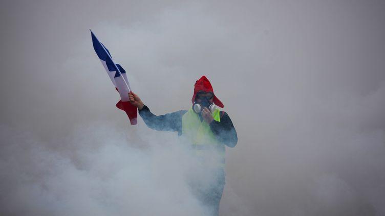 """Un """"gilet jaune"""" dans un nuage de gaz lacrymogène à Paris, le 1er décembre 2018. (THEO LEGENDRE / AFP)"""