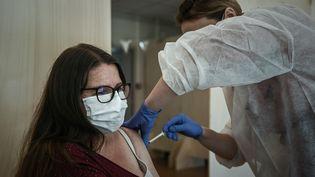 Une patiente se fait vacciner contre le Covid-19, le 26 mai, à Bordeaux, dans le quartier Bacalan où une nouvelle forme du virus est apparue. (PHILIPPE LOPEZ / AFP)